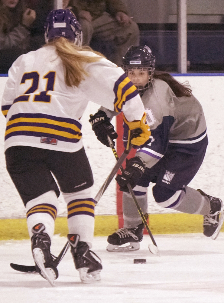 Emma Merrill of Portland/Deering looks for an opening against Abby Enck of Cheverus/Kennebunk during the City Cup girls' hockey game Monday at Troubh Ice Arena. Portland knocked off the previously undefeated Stags, 4-3 in overtime.