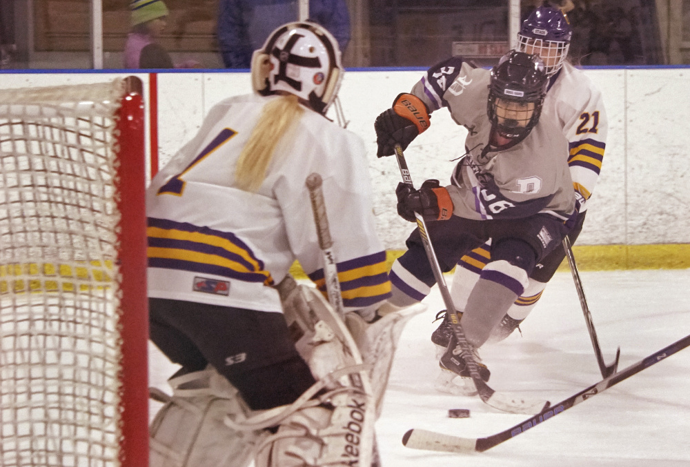 Emily Demers of Portland/Deering prepares to shoot against Cheverus/Kennebunk goalie Anna Smith. Demers scored a third-period goal to help the Bulldogs pull out a 4-3 overtime victory.