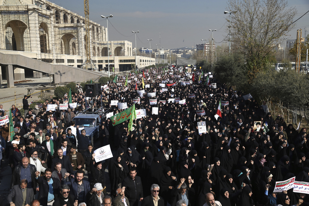 Iranian protesters chant slogans at a rally in Tehran on Saturday. Iranian hard-liners rallied Saturday to support the country's supreme leader and clerically overseen government as spontaneous protests sparked by anger over the ailing economy roiled major cities in the Islamic Republic.