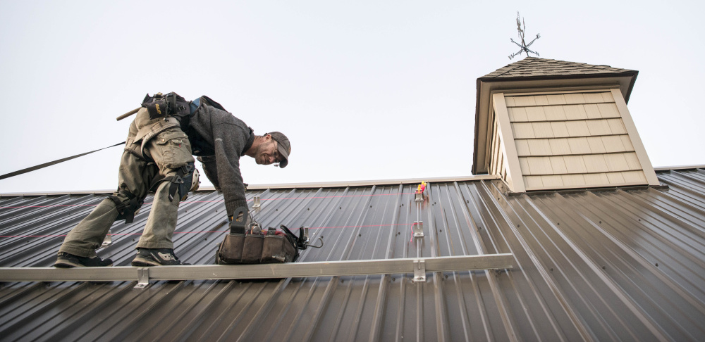 Andrew Legere, with ReVision, installs a solar array on a building at Rocky's Stove Shoppe in Augusta on Dec. 6. Rocky's was Maine's first stove shop to convert to solar.