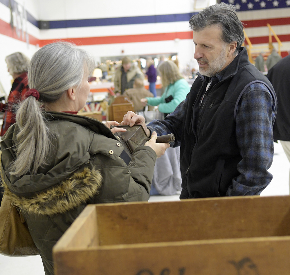 David McLean speaks with customer Julia Gagne at his booth Monday at the New Year's Day Antiques Show at the Augusta Armory.