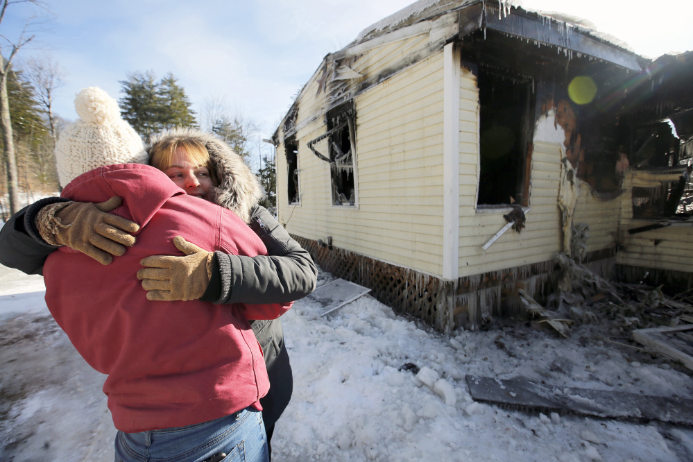 Cherie Eastman, right, hugs Kira Harmon while surveying Eastman's fire-damaged home on Tuesday morning. Eastman maintained her sense of humor during the tour, joking that the fire destroyed the home she designed and built with her husband and late father, but somehow spared a stack of cordwood, the back deck, and a nearby shed that she considers an eyesore.