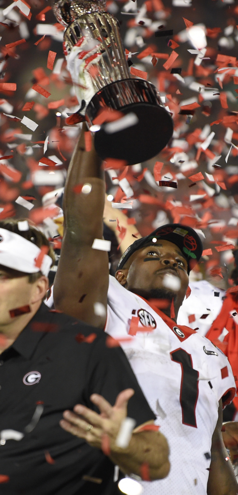 Georgia running back Sony Michel holds the Rose Bowl trophy Monday after scoring the overtime touchdown that beat Oklahoma 54-48 and put the Bulldogs into the final against Alabama.
