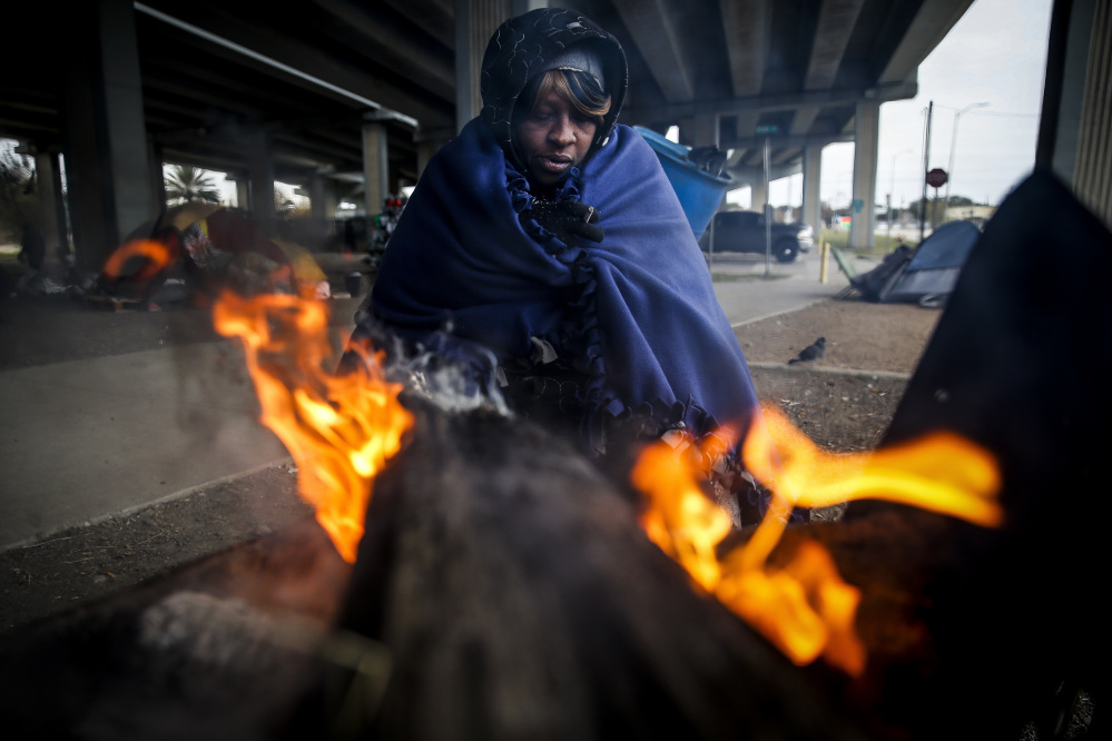 Tony Sampson, who received a blanket from Star of Hope's Love in Action van, tries to warm up by a fire under the Eastex Freeway as temperatures hover in the 30s Tuesday n Houston. Plunging overnight temperatures in Texas brought rare snow flurries as far south as Austin, and accidents racked up on icy roads across the state.