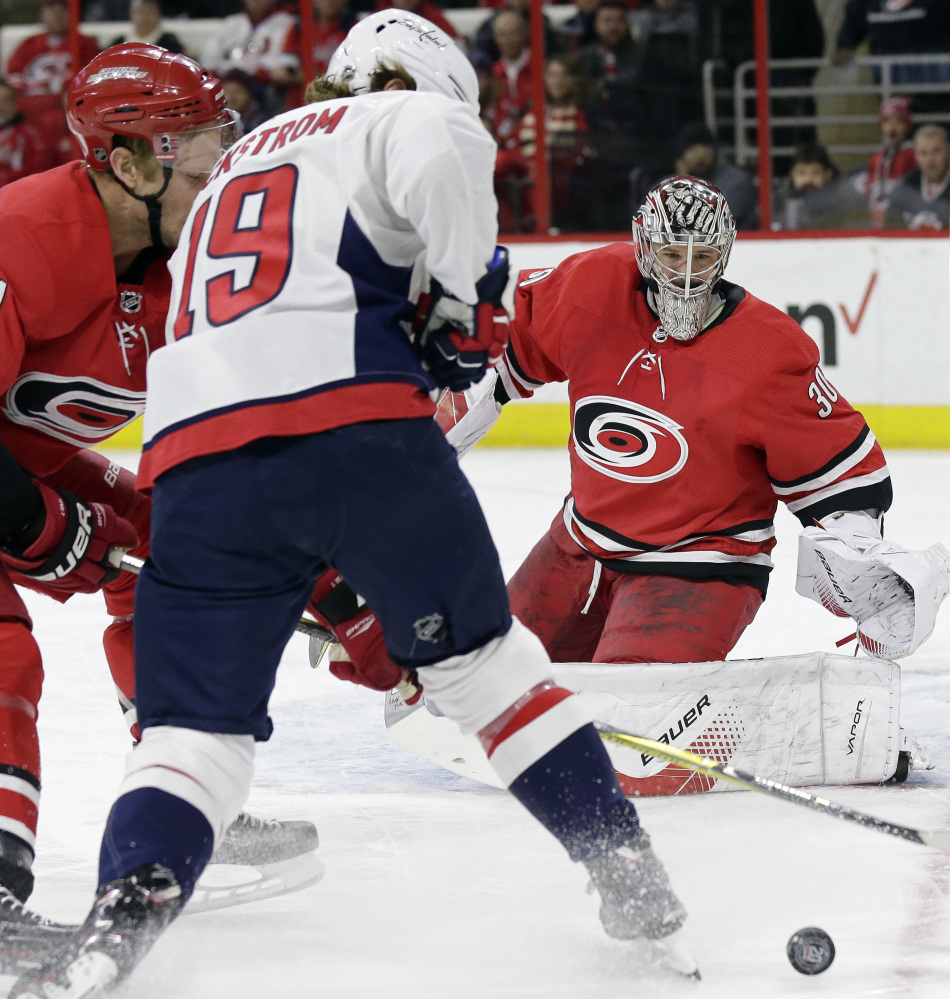 Hurricanes goalie Cam Ward keeps an eye on the puck while Jordan Staal and Washington's Nicklas Backstrom battle for the puck in the first period Tuesday night in Raleigh, N.C.