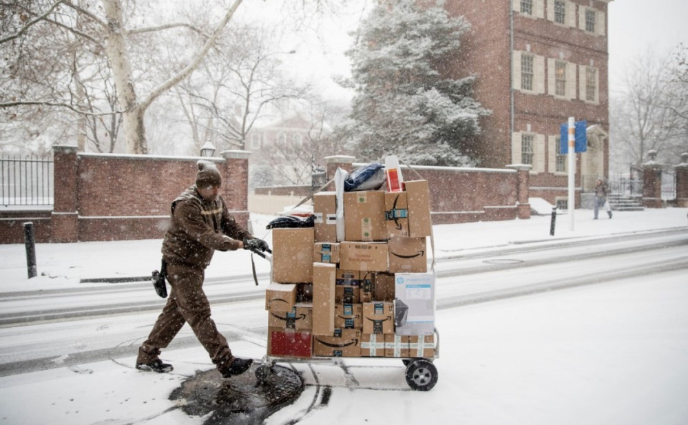 A United Parcel Service worker makes his deliveries during a snowstorm in Philadelphia on Dec. 15. An estimated 25-30 percent of online purchases are sent back, about triple the rate for items bought in-store.