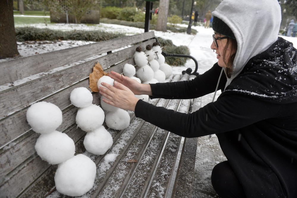 Savannah College of Art and Design student Helene Fischer fashions a small snowman on a park bench in Forsyth Park on Wednesday morning in Savannah, Georgia. Fischer, who is from Florida, experienced snow for the first time.