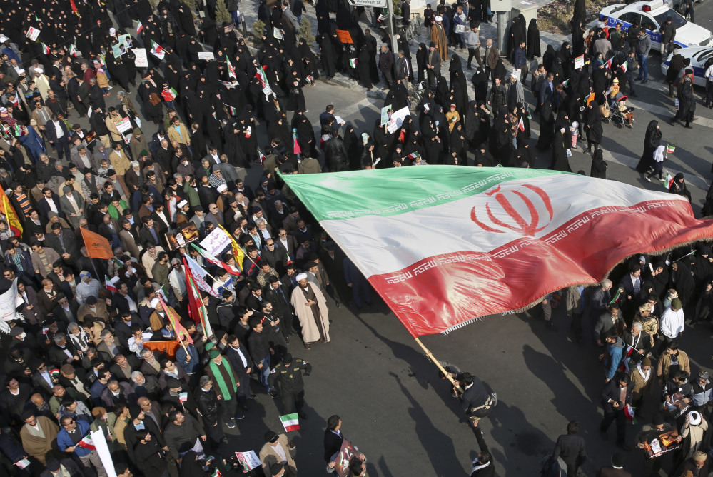 A pro-grovernment demonstrator waves an Iranian flag during a rally in the northeastern city of Mashhad, Iran, on Thursday. Few photos of anti-government demonstrations have been published during a week of unrest.