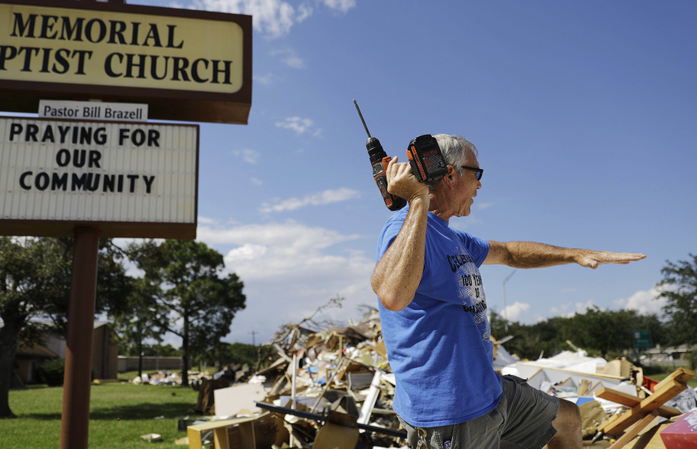 Wayne Christopher sifts through debris outside his damaged church from Hurricane Harvey in Port Arthur, Texas, last fall.