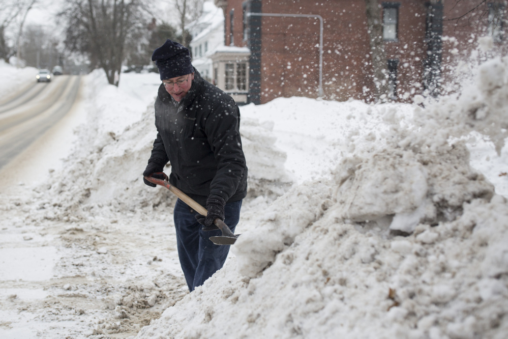 Mark Fisher shovels snow out of the way to widen his driveway in the single digit temperatures on Saturday. Inland Maine could see record breaking cold overnight on Saturday into Sunday.