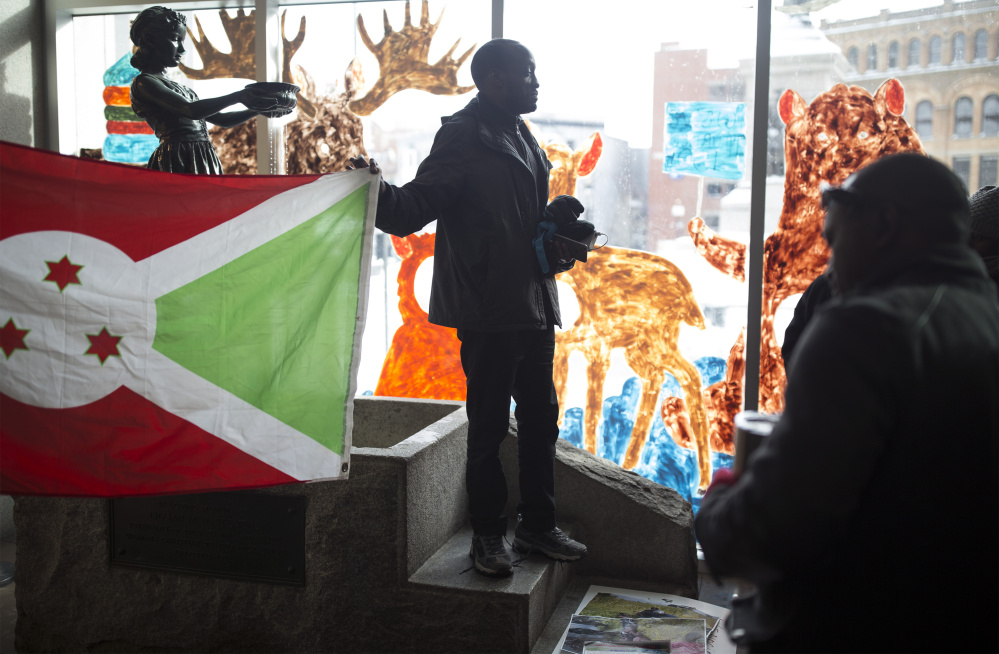 Philemon Dushimire holds up the Burundian flag Saturday as he talks to protesters inside the Portland Public Library after their demonstration in Monument Square. A group of about 25 to 30 people protested relocation of a high-ranking Burundian official's family in Maine.