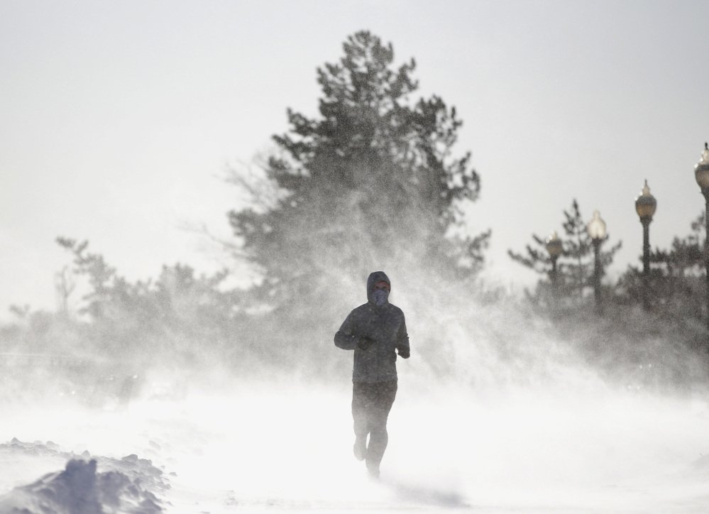 Gusty wind picks up snow accumulated on the ground as Jesse Sherwood of Jersey City, N.J., jogs Saturday in Jersey City. About 100 million people faced a new challenge after the whopping East Coast snowstorm: a deep freeze, topped Saturday by a wind chill.