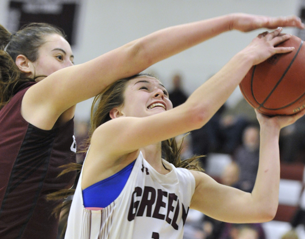 Mackenzie Holmes of Gorham tries to block a shot by Greely's Camille Clement but gets called for a foul. Holmes spent much of the game in foul troubled but still scored 21 points, while Clement finished with 13 points.