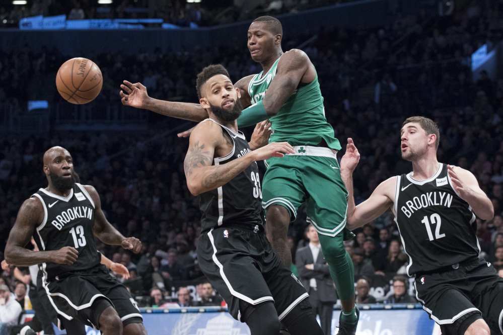 Boston Celtics guard Terry Rozier, center, moves the ball around Brooklyn Nets guard Allen Crabbe (33) during the second half of an NBA basketball game Saturday, Jan. 6, 2018, in New York.