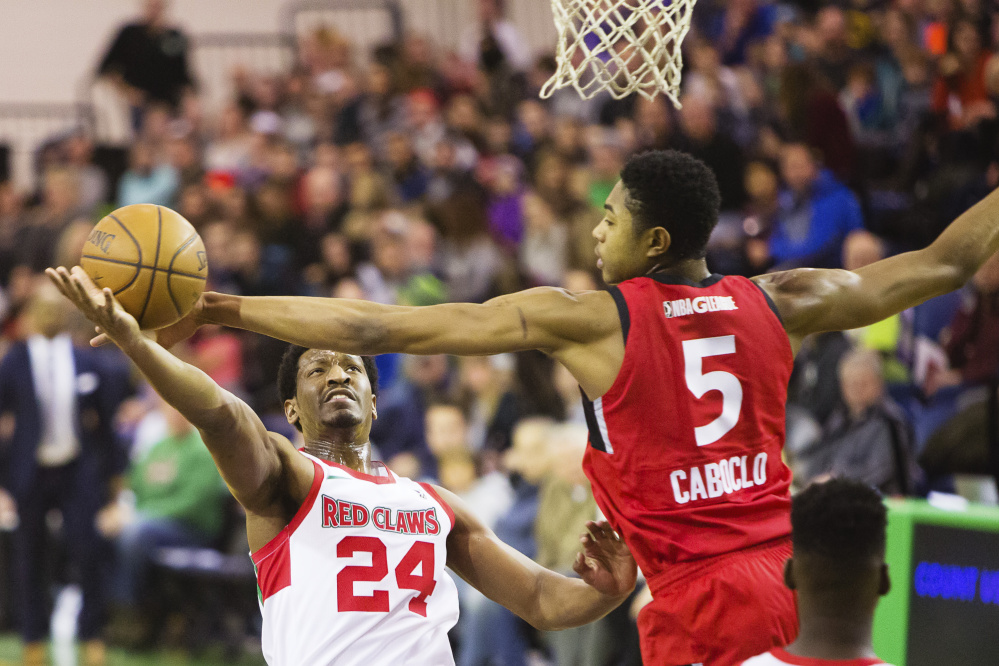 Maine forward Andrew White takes a shot while defended by Bruno Cabocio of Raptors 905 during the Red Claws' 100-93 loss Sunday at the Portland Expo.