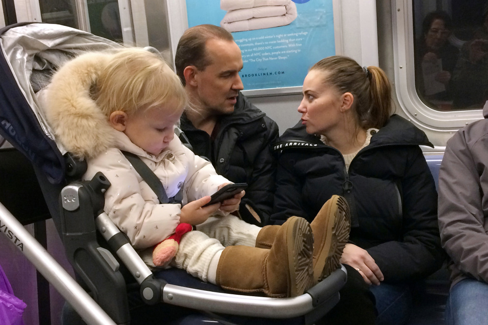 A child plays with a cellphone while riding in a New York subway last month. There are growing concerns about the long-term impact of gadgets and social media on the young, especially those who use smartphones at an early age.