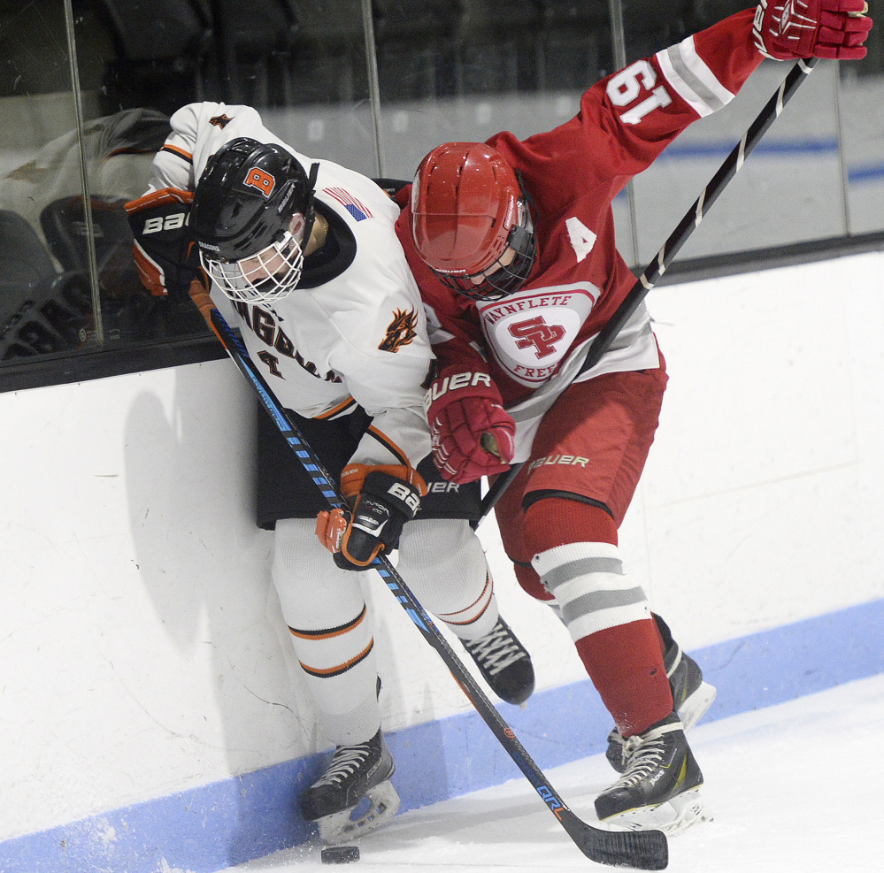 Brunswick's Jack St. Pierre, left, and Mitchell Adams of South Portland/Freeport/Waynflete battle along the boards Monday at Watson Arena. Adams had a goal and two assists in the Red Riots' 5-2 victory.