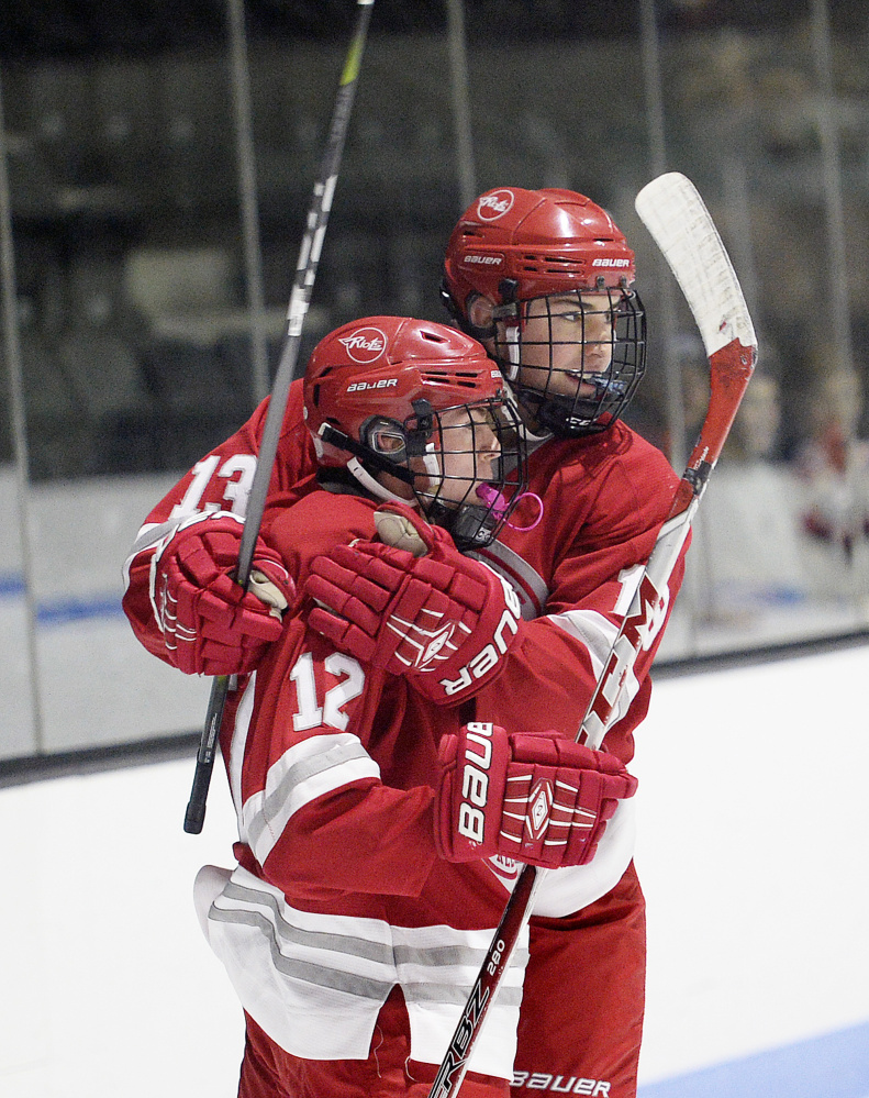 Aidan Schifano, left, celebrates with South Portland/Freeport/Waynflete teammate Devan Hannan after the first of Schifano's two goals Monday.