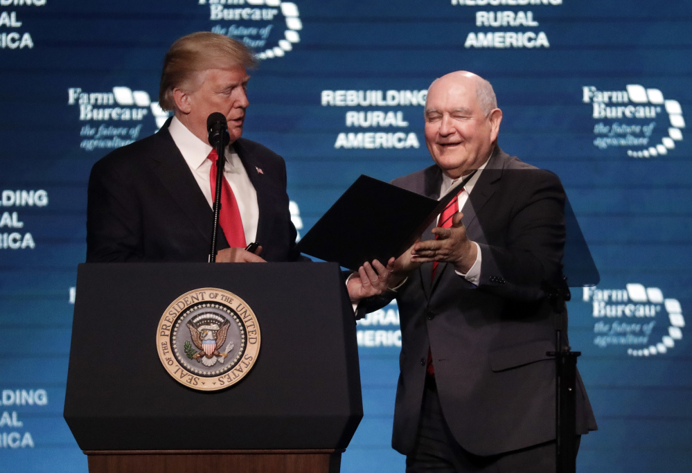 President Donald Trump hands an executive order to Secretary of Agriculture Sonny Perdue, right, after reading it at the American Farm Bureau Federation annual convention Monday in Nashville, Tenn.
