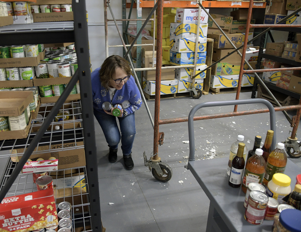 Augusta Food Bank employee Susan Williams collects groceries Monday next to staging erected at the new facility so contractors could fix the leaking roof.