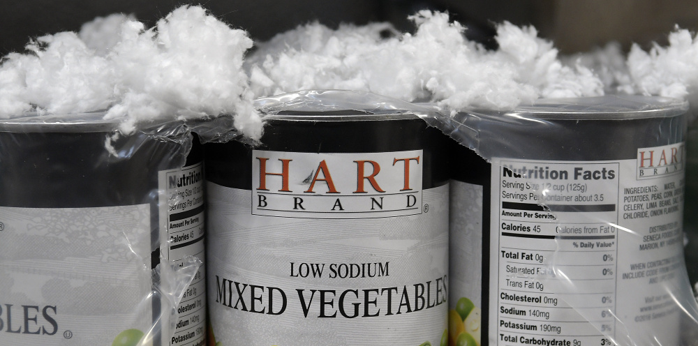 Canned goods covered with insulation at the Augusta Food Bank on Monday after water leaked through the new facility on Mount Vernon Avenue.