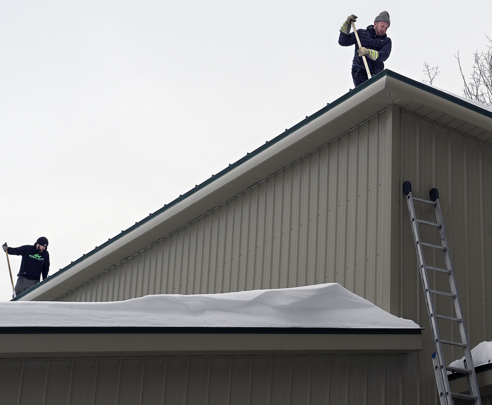 Workers remove snow from the roof of the food bank on Monday after water leaked in, likely because of ice dams.