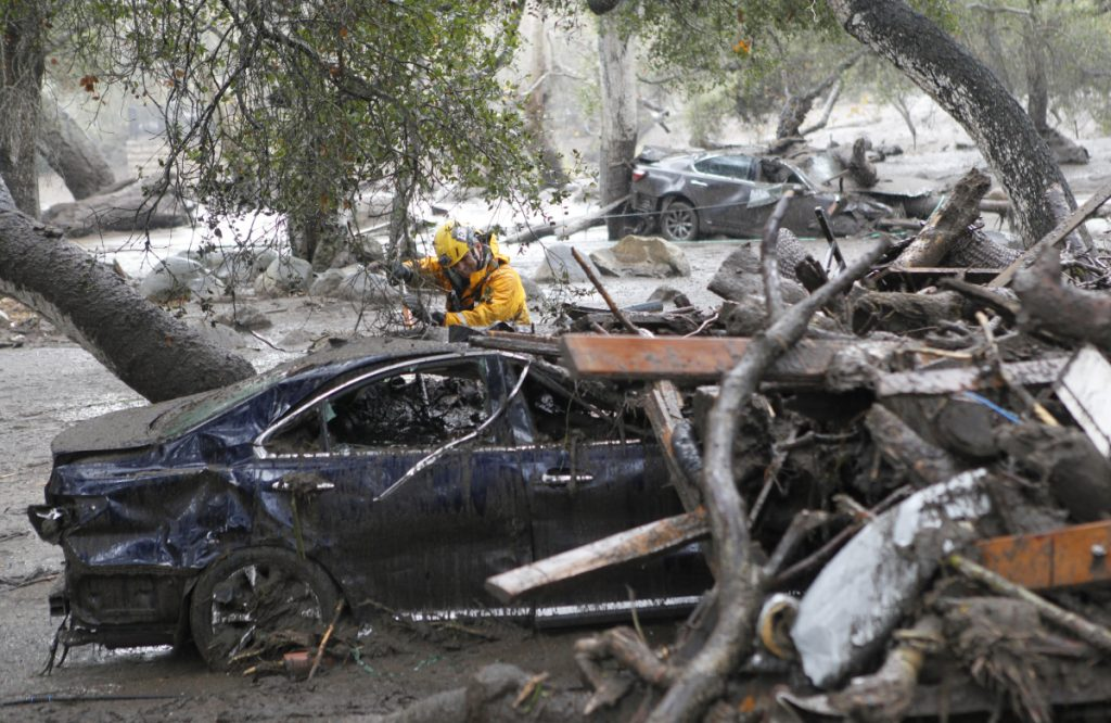 A member of the Long Beach Search and Rescue team looks for survivors in a car in Montecito, California, on Tuesday.