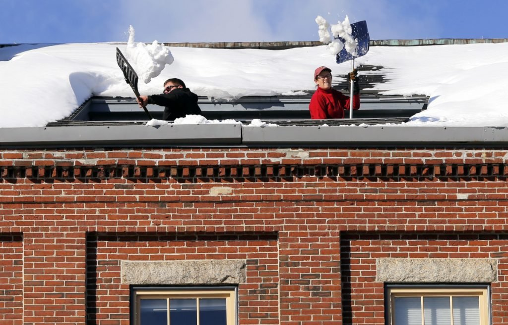 Joe Hebert, left, and Leza Gough shovel snow Tuesday from a rooftop deck on the fifth floor of 269 Commercial St. in Portland. Additional workers on the sidewalk below were diverting pedestrians away from the falling snow.
