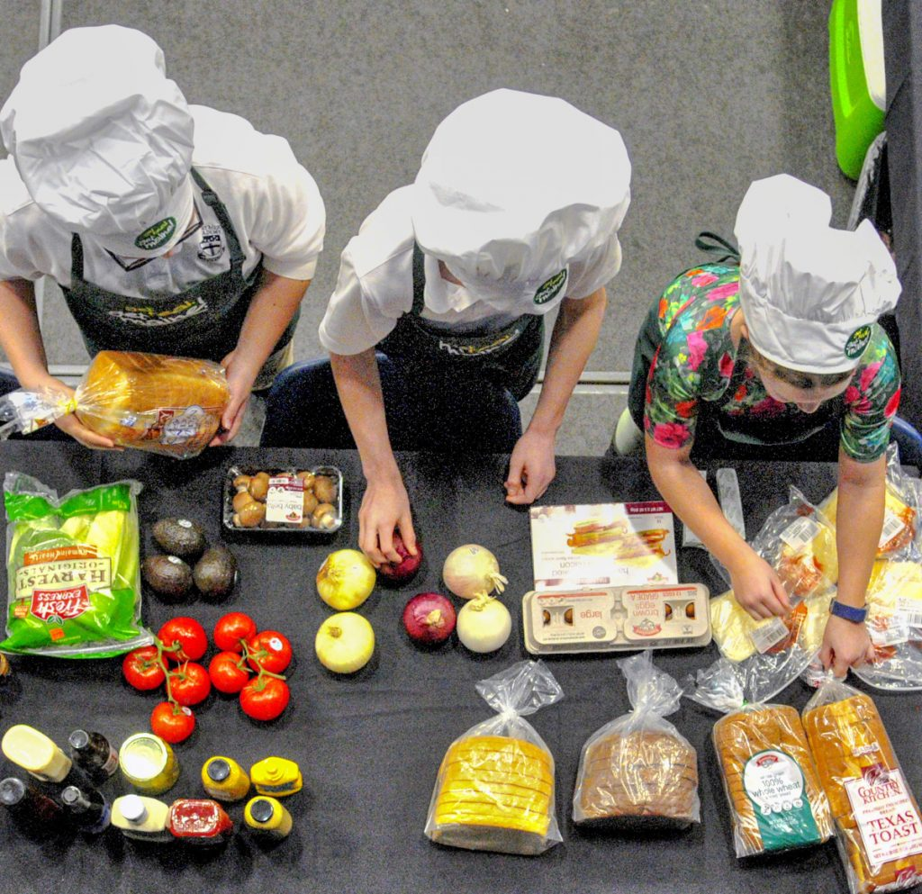 Contestants search the pantry at the start of their half hour allotted for a grilled cheese sandwich cooking contest Wednesday at the 77th annual Agricultural Trades Show in the Augusta Civic Center.
