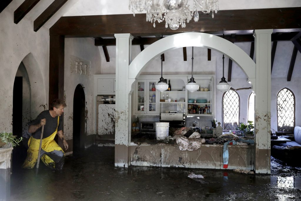 Bill Asher walks through knee-deep mud in his Montecito, Calif., home Thursday. As many in the flood-stricken area turned to reclaiming their homes, rescue workers continued their search for victims.