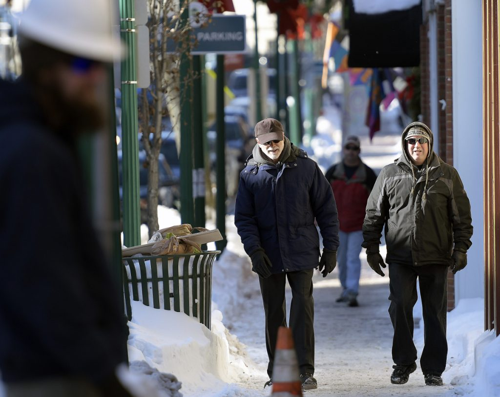 People walk along Water Street on Wednesday in Gardiner with high snowbanks lining the sidewalk.