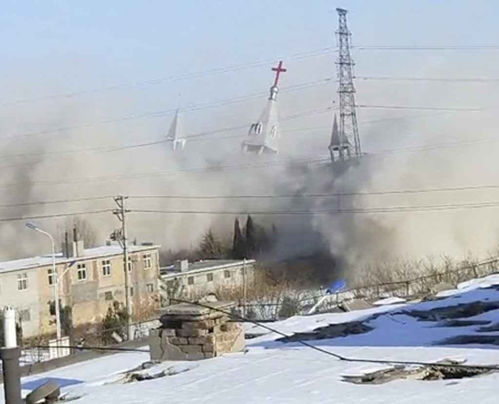 An image taken from a video shot Tuesday shows the Golden Lampstand Church in Linfen, China, coming down in a cloud of dust and debris.