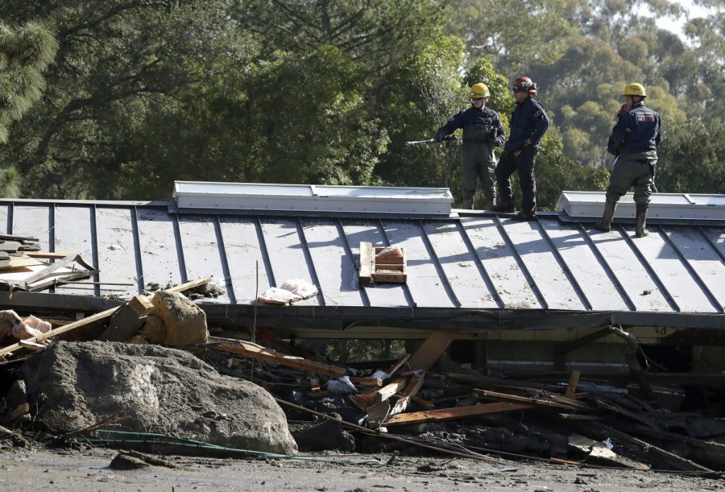 Emergency crew members search an area near houses damaged by storms in Montecito, Calif., on Friday.