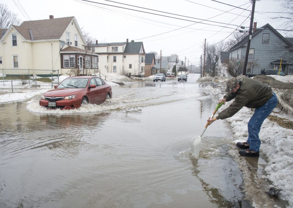 Dave Pullo, of Boston, clears a drain on Oak Street to help drain flood waters that extended down Drummond Avenue to High Street in Waterville on Saturday, Jan. 13, 2018.