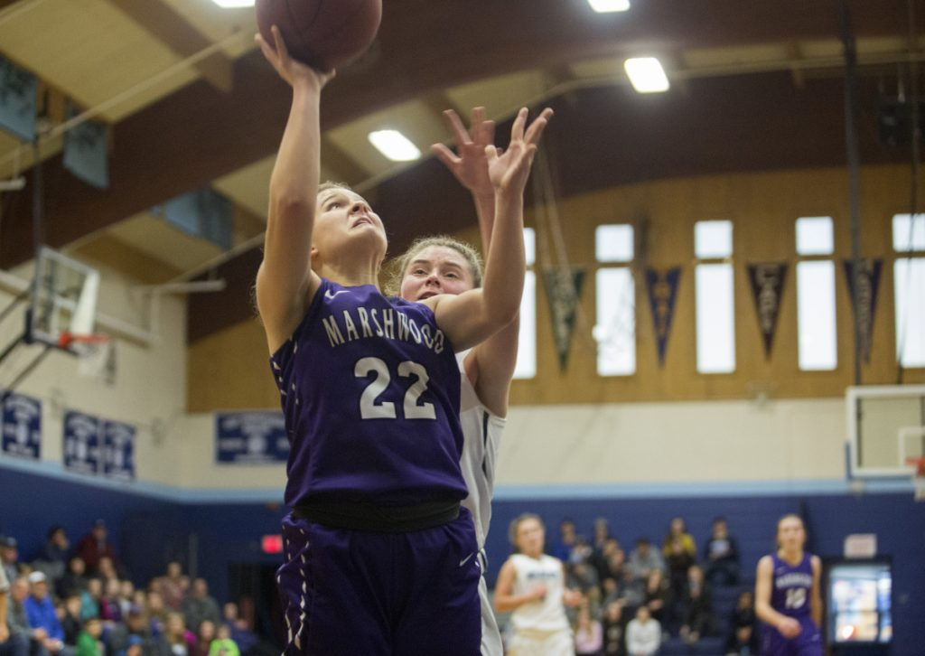 Marshwood's Elora Montgomery drives to the basket against Kristen Leroux of York and makes a layup during her team's 35-27 win Saturday afternoon in York.