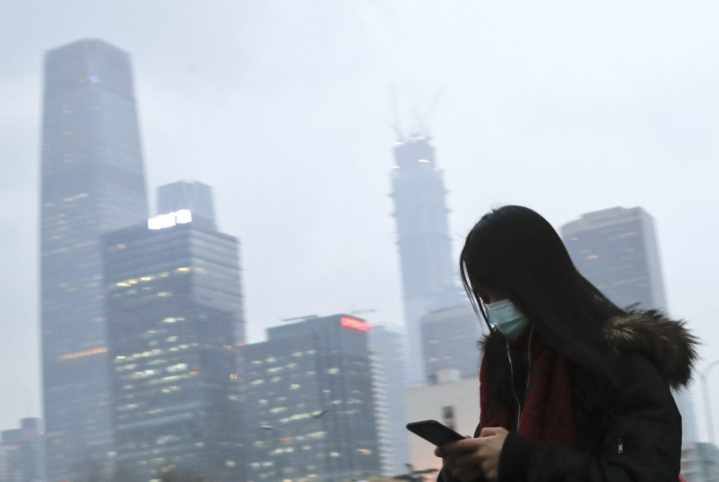 Associated Press/Andy Wong A woman wears a mask last year in Beijing. Environmental inspectors traveled to outside cities forcing factories and homes to move to natural gas and cease using coal.