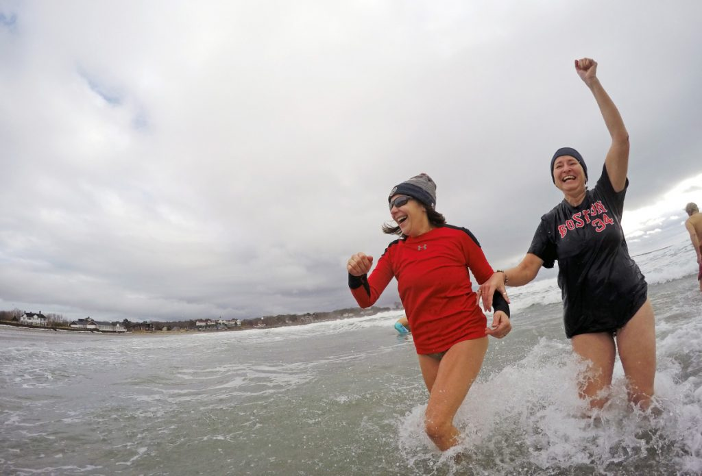 Above, Abraham Boulter, center, of Sanford, bounds into the frigid water at Kennebunk's Gooch's Beach on Saturday morning for the 17th annual Atlantic Plunge. At top, Diana Onacki, right, with her unidentified plunge partner, raises her hand in victory after emerging from the 41-degree water. The event benefits a York County center for victims of abuse.
