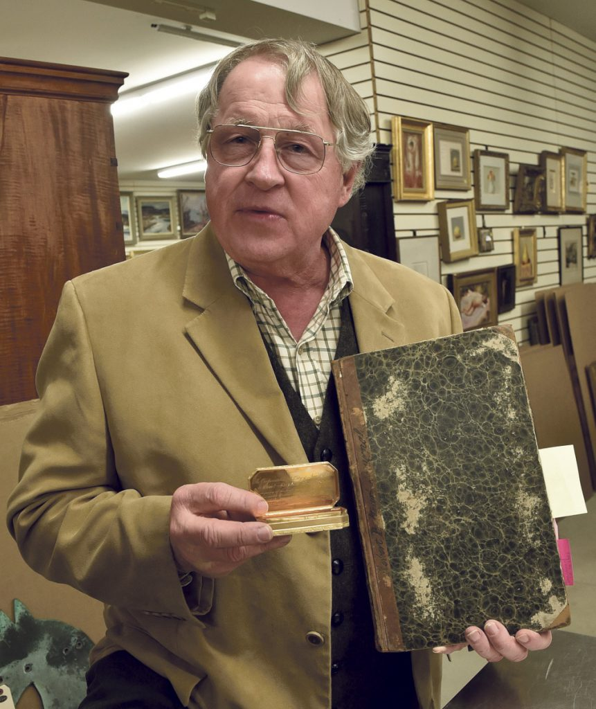 Auctioneer Jim Julia, 71, displays a Freedom box and a ship's log from the USS Constitution that could sell at auction for $200,000 each.