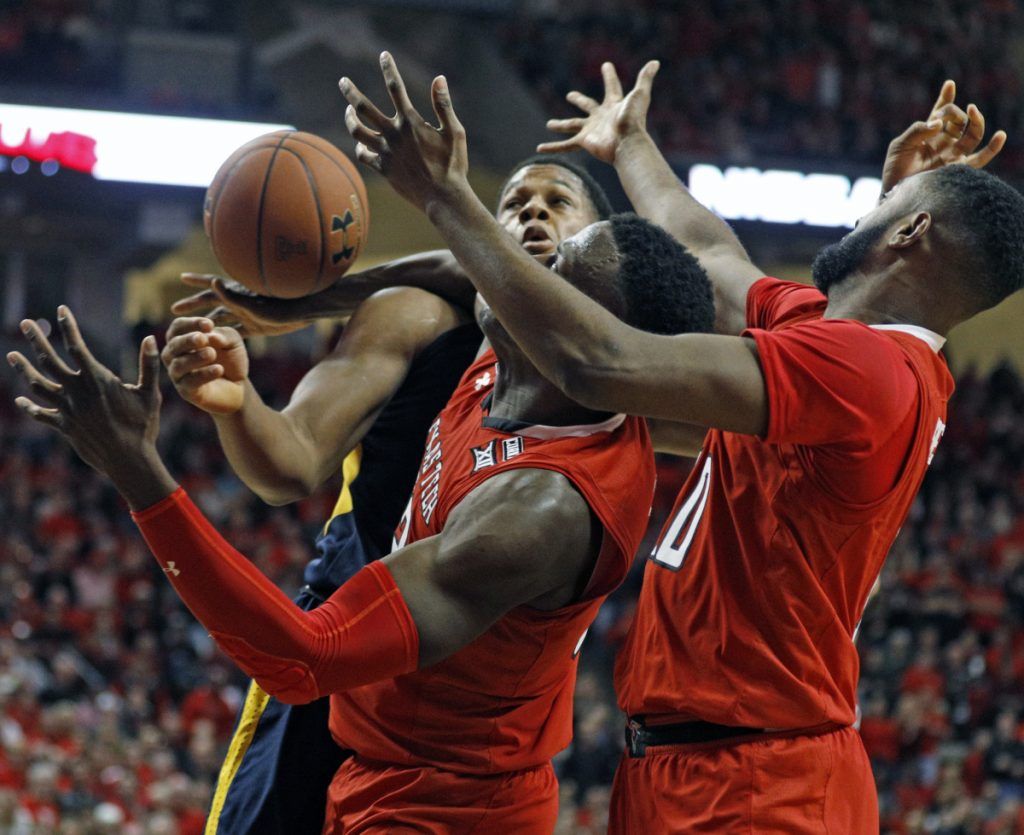 Sagaba Konate of West Virginia, left, competes for a rebound with Norense Odiase, center, and Niem Stevenson of Texas Tech during the second half of Texas Tech's 72-71 victory Saturday. Texas Tech was ranked No. 8 and West Virginia was No. 2.