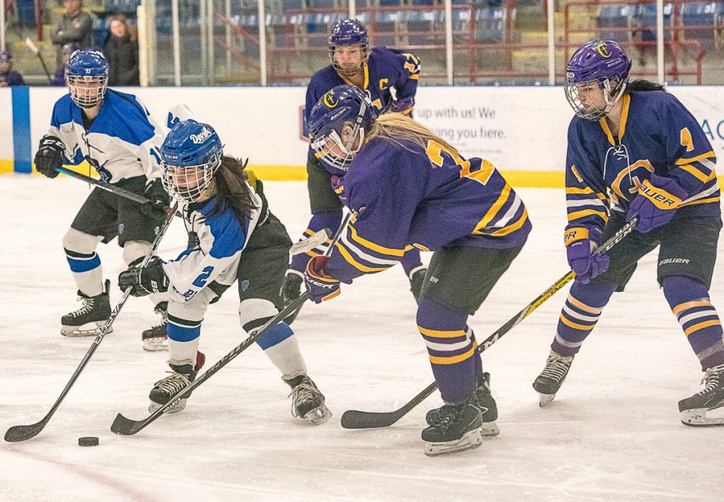 Lewiston's Madison Conley maneuvers around Abby Enck of Cheverus/Kennebunk during Saturday night's game at the Androscoggin Bank Colisee. Cheverus/Kennebunk won in overtime, 4-3.