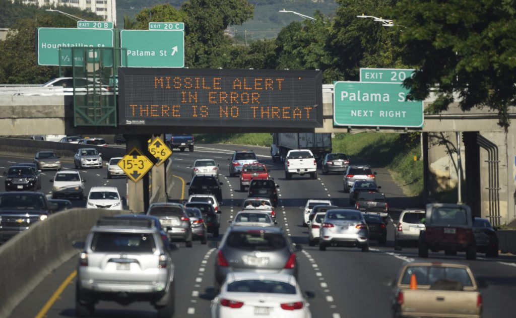 In this Saturday, Jan. 13, 2018 photo provided by Civil Beat, cars drive past a highway sign that says
