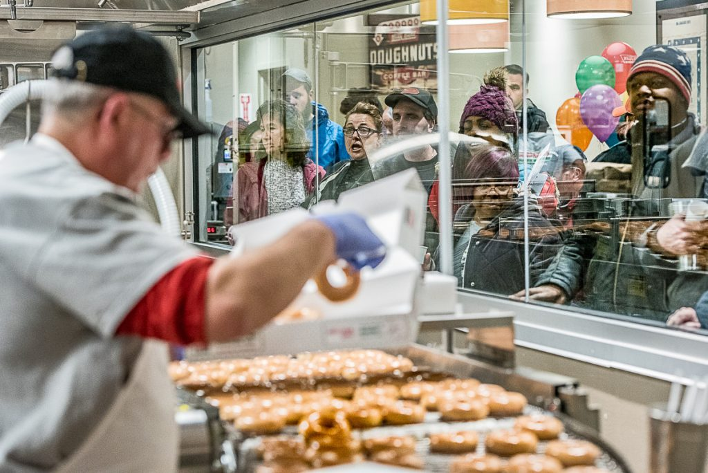 """Customers watch the hot doughnuts coming off the line at Krispy Kreme in Auburn during the grand opening Monday morning. People waited outside in the cold for as long as 15 hours before the store switched on its """"Hot Now"""" light at 6 a.m. .."""