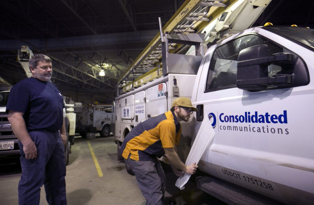 "Fleet mechanic Steve Morin watches as Chris Bagley of Sebago Signworks pulls off the covering of a new Consolidated Communications logo after applying it to the door of a former FairPoint truck. ""It's a new chapter for us. It's a rededication to our customers,"" said Rob Koester, Consolidated's vice president for consumer products."