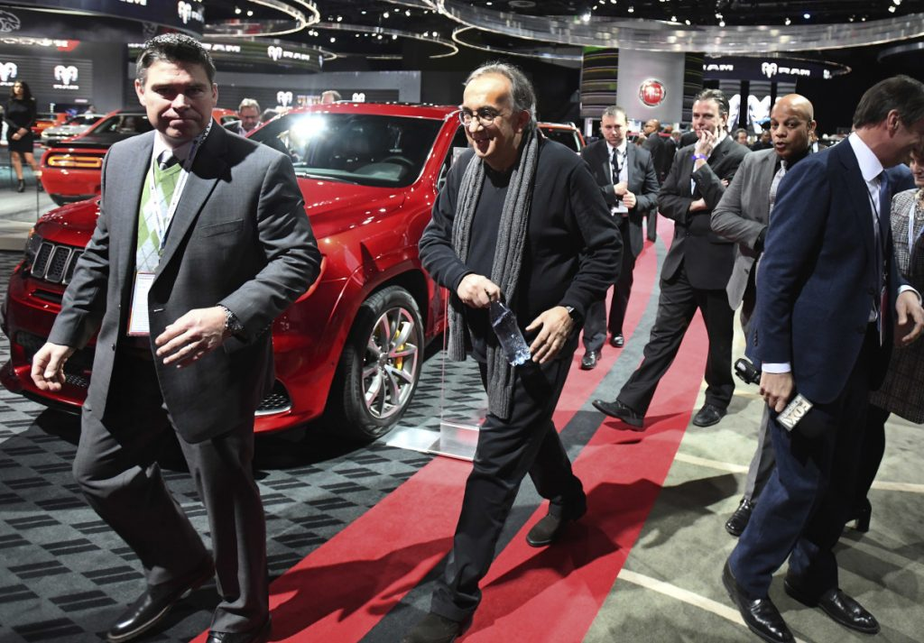 Fiat Chrysler Automobiles CEO Sergio Marchionne, center, walks the floor Monday at the North American International Auto Show in Detroit. He said he'll step down in 2019.