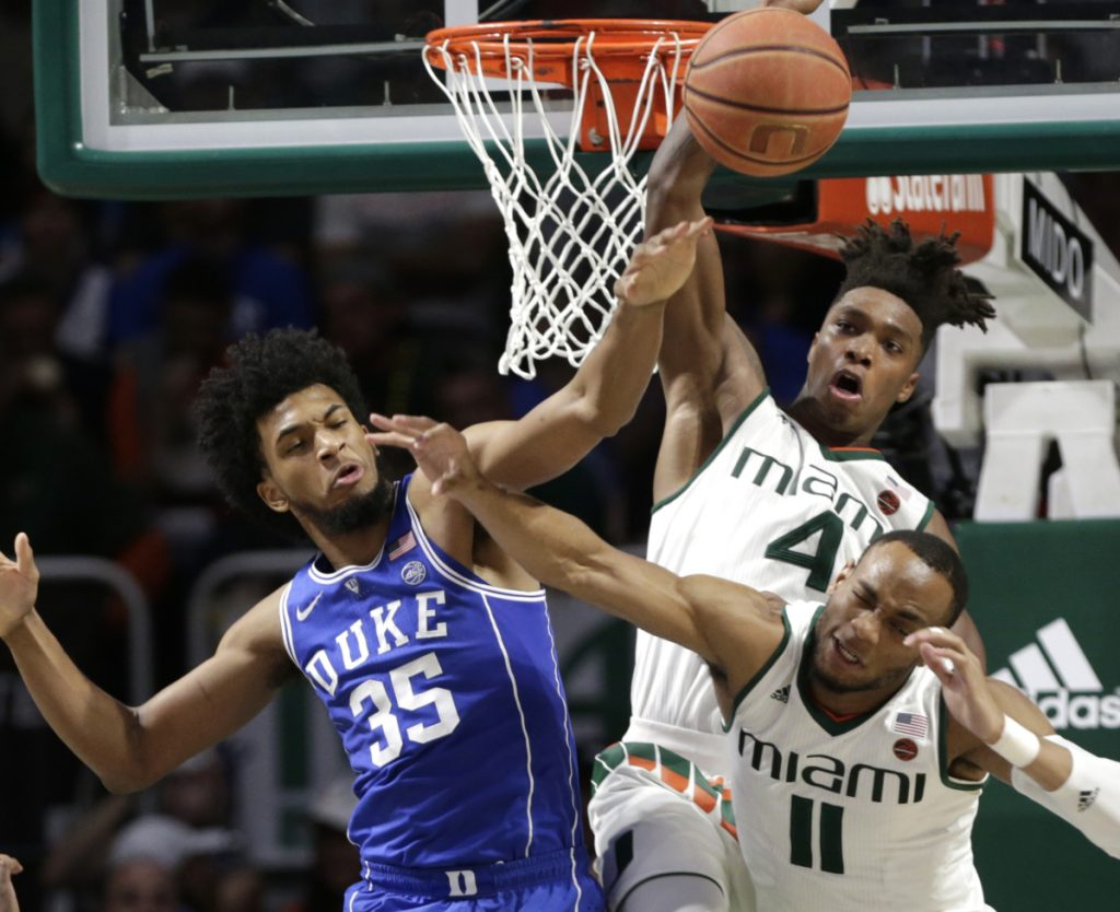 Duke's Marvin Bagley III, Miami's Lonnie Walker IV, 4, and Bruce Brown Jr., 11, all fight for a rebound during the Blue Devils' 83-75 win Monday in Coral Gables, Florida.