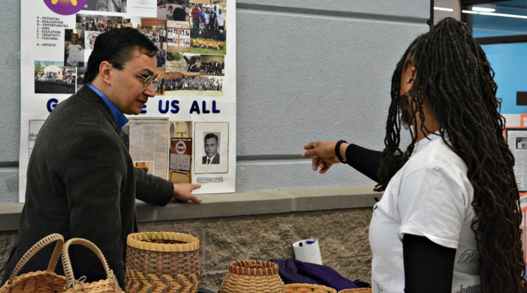 Cherokee Nation Secretary of State Chuck Hoskin Jr., left, looks over an exhibit during a visit Monday to the Martin Luther King Community Center in Muskogee, Okla.