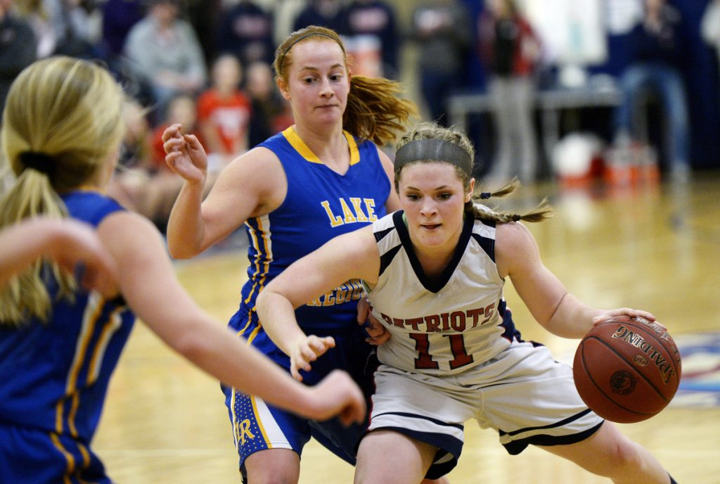 Gray-New Gloucester's Alexa Thayer drives with the ball as Bella Russo of Lake Region moves in on defense during the Patriots' 42-41 win Tuesday in Gray.