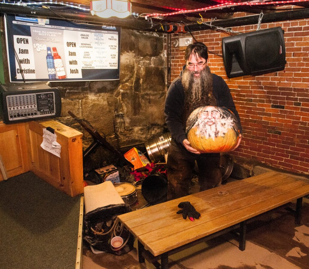 Bartender Dave Pottle recovers a pumpkin with his face painted on it from a pile of stools and kegs Tuesday in the back corner of the Hydeout at The Wharf in Hallowell.
