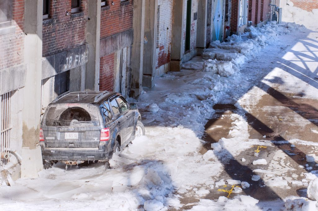One vehicle remains frozen in ice late Tuesday morning in the Front Street parking lot in Augusta.