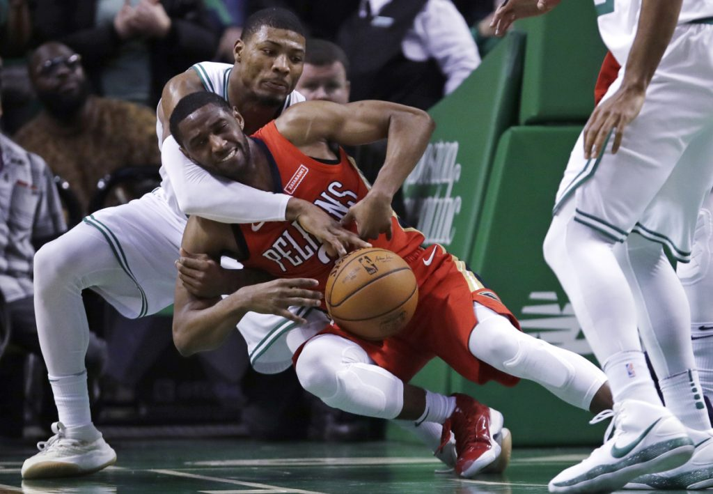 Boston's Marcus Smart, rear, reaches around and knocks the ball from the hands of New Orleans Pelicans guard Ian Clark in the second half Tuesday night in Boston.